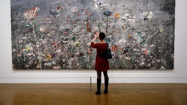 Eine Frau steht vor einem Bild von Anselm Kiefer.