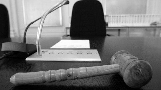 Ein Gerichtshammer liegt auf der Anklagebank.