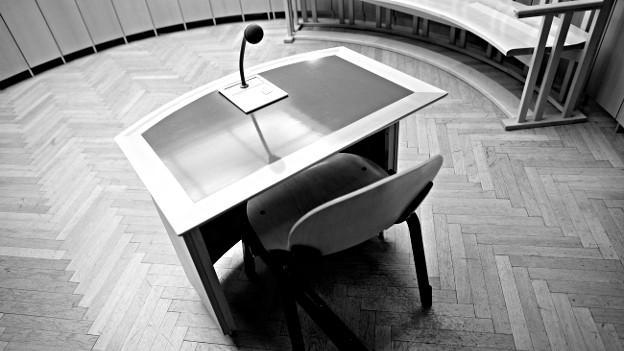 Ein Tisch mit Mikrofon in einem Gerichtssaal.