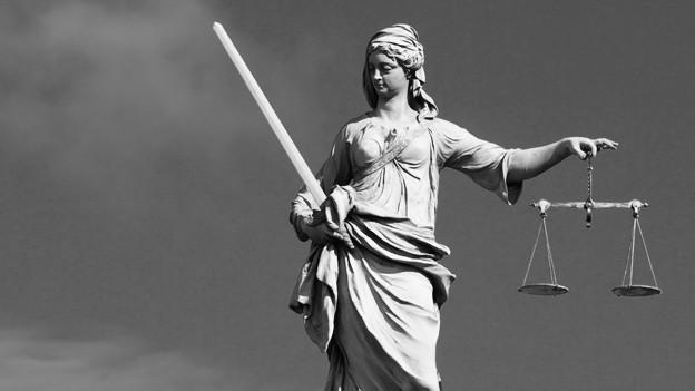 Auf dem Bild ist vor blauem Himmel eine steinerne Figur von Justizia zu sehen.