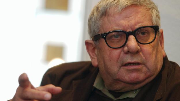 Das Bild zeigt den Schweizer Autoren Hugo Loetscher mit dunkler Hornbrille.
