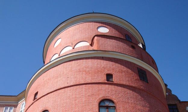 Ein rötlicher, runder Turm vor blauem Himmel.