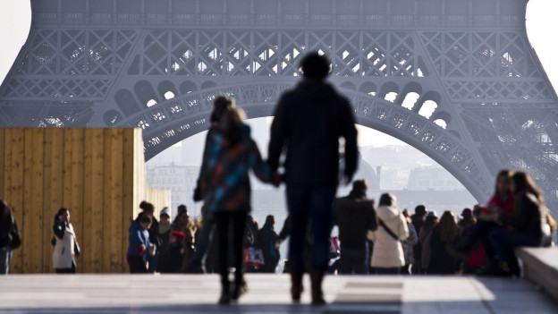 Ein Pärchen hält die Hand und spaziert. Im Hintergrund sieht man den Eiffel Turm in Paris.