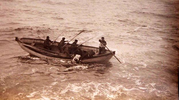 Eine alte Sepia-Fotografie zeigt ein Rettungsboot auf hoher See.