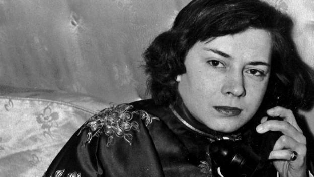 Eine schwarz-weiss Aufnahme der jungen Patricia Highsmith mit Telefonhörer am Ohr.