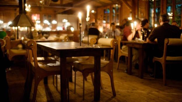 Kerzen auf einem ungedeckten Tisch in einem rustikalen Restaurant. Im Hintergrund sind ein Cheminée und mehrere besetzte Tische zu erkennen.