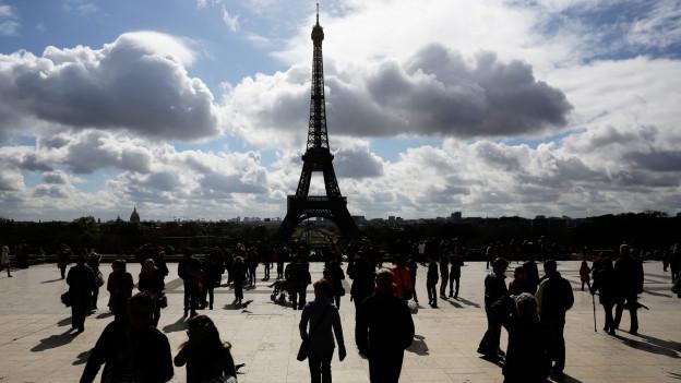 Der Eiffelturm ist im Hintergrund. Vorne gehen Menschen.