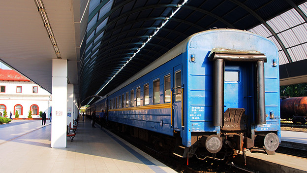 Blauer Zug mit Waggons im bahnhof.
