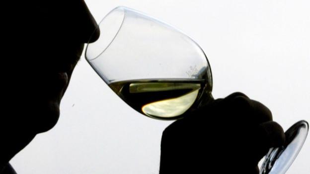 Ein Mann trinkt Wein. Das Foto ist schattig.