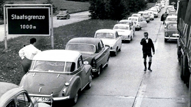 1940er Jahre: Stau, auf der Seite kündigt ein Verkehrschild die Grenze in 1000 Metern an.