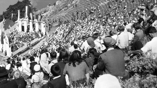 Schwarz-Weiss-Aufnahme aus den 50er-Jahren: Publikum sitzt bei einem Festspiel in einer Freilufttribüne.