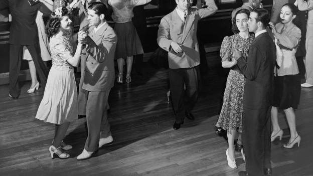 Tanzende Paare bei einem Fest, im Hintergrund eine Big-Band, Aufnahme aus den 50er-Jahren.