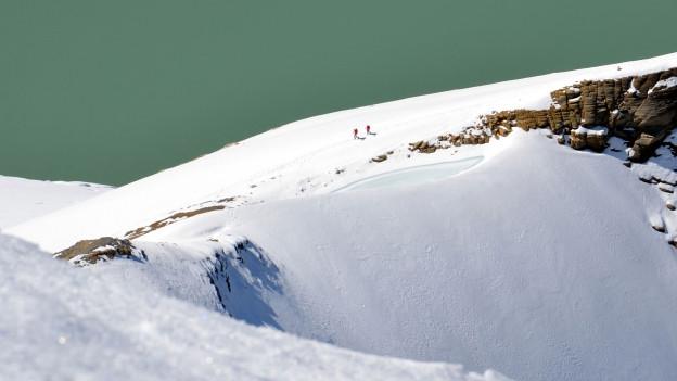 Zwei Bergsteiger in der Ferne auf einem verschneiten Gipfel.