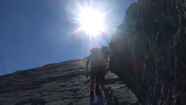 Zwie Bergsteiger im Gegenlicht an einem steilen Felshang.