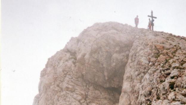 Zwei Männer stehen neben einem Gipfelkreuz.