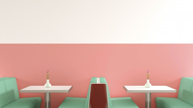Zwei leere Tische in einem amerikanischen Diner, Wände und Stühle sind in Pastellfarben gehalten.