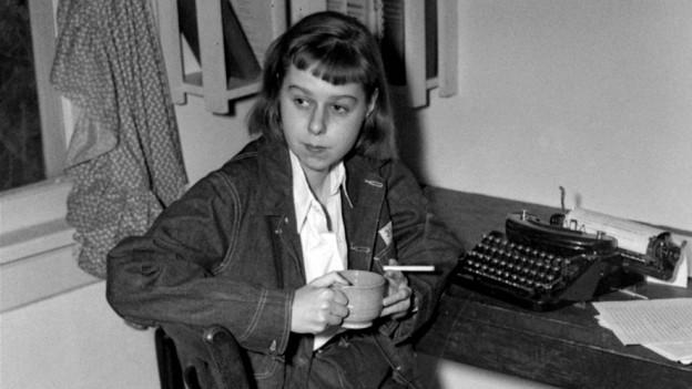 Eine Frau sitzt an einem Tisch, auf dem eine Schreibmaschine steht. In der Hand hält sie eine Tasse und eine Zigarette.