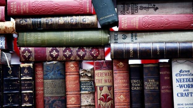 Englische, alte Bücher aneinandergereiht und aufeinandergestapelt.