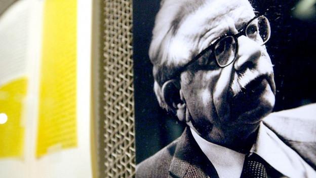 Eine Fotografie eines Mannes liegt neben einem aufgeschlagenen Buch.