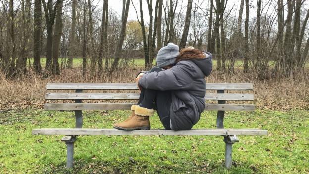 Eine Frau sitzt zusammengekauert auf einer Parkbank.