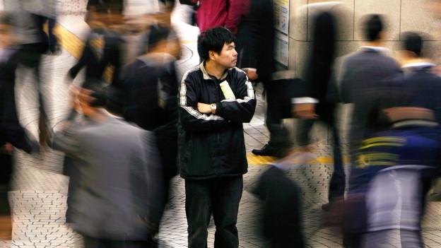 Leute laufen an einem Mann vorbei, der am Shinjuku Bahnhof in Tokyo steht.