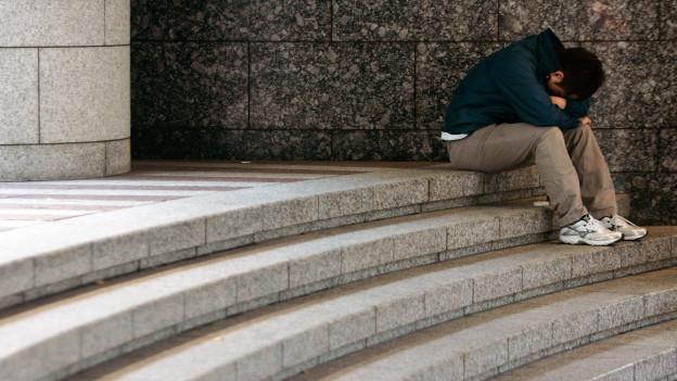 Ein verzweifelter Mann sitzt auf einer Treppe.