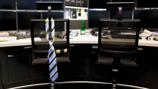 Symbolbild: Eine Krawatte hängt einsam über einem Bürostuhl.