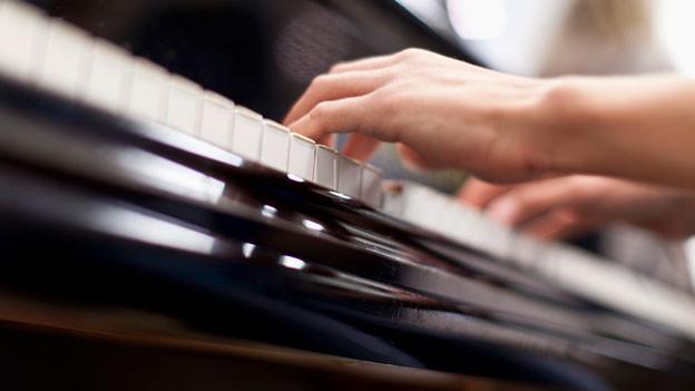 Ein Kind spelt Klavier.
