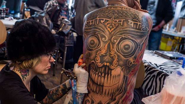 Man sieht eine Frau, die den Rücken eines Kunden tätowiert.