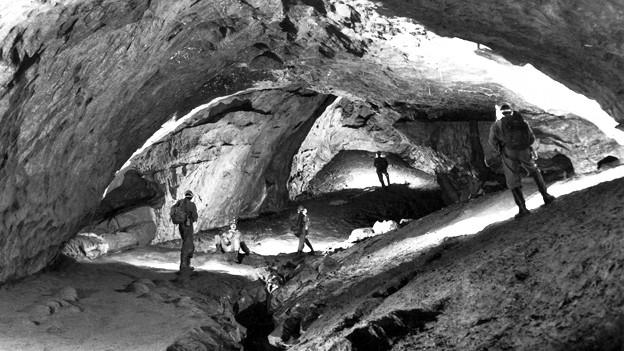 Menschen stehen in einer riesigen Höhle.