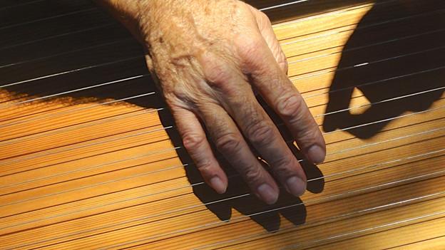 Abbildung von Händen, die auf einem Zupfinstrument spielen.