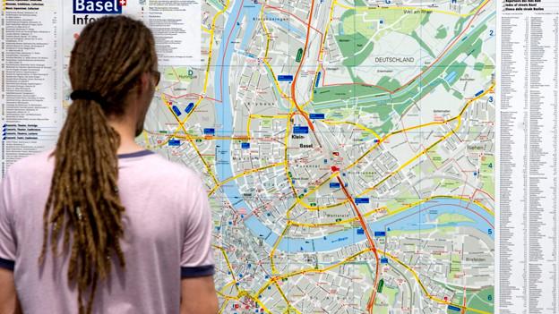 Mann steht vor Stadtplan von Basel.