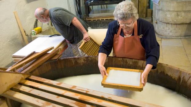 Papierschöpfen in der Papiermühle.