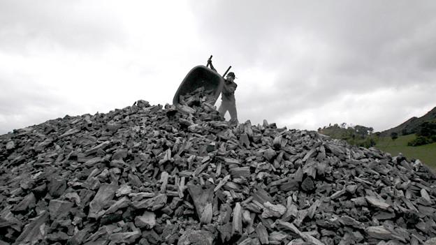 Ein Haufen Kohle, ein Mann leehrt eine Schubkarre aus.