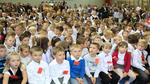 Kinder warten in einem grossen Saal.