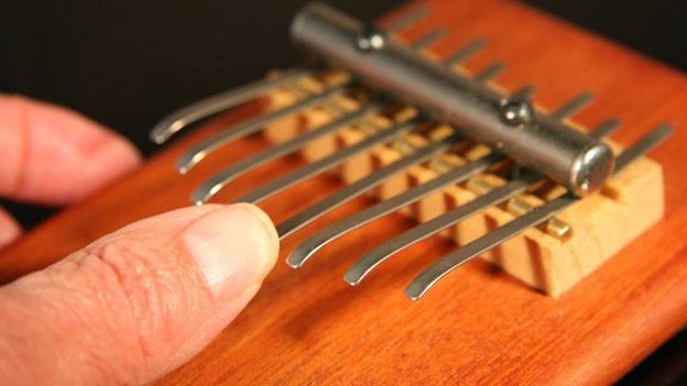 Die Hand eines Menschen spielt auf einer Kalimba (Musikinstrument)