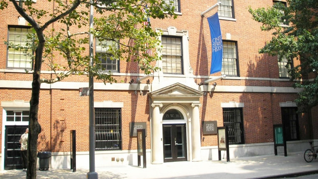 """Blick auf ein Backsteingebäude mit einer Flagge. Darauf steht """"Center for Jewish History"""""""