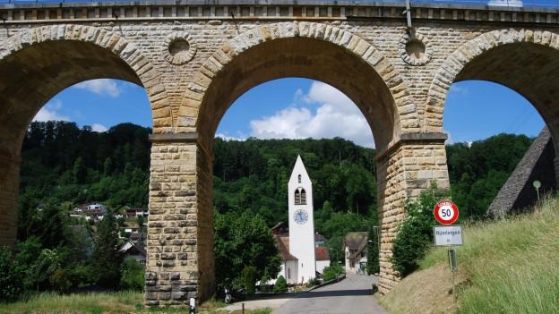 Durch den Bogen eines Bahnviadukts sieht man den Dorfeingang und die Kirche Rümlingens.