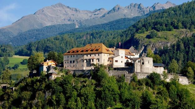 Burg umgeben von Wald und Bergen