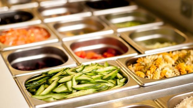 Essen in Metallschalen einer Kantine.