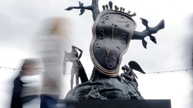 Eine Skulptur, die eine zerfliessende Uhr zeigt.