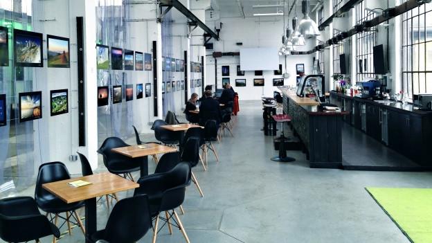 Ansicht auf eine Bar im Industriestil mit Fotografien an den Wänden.