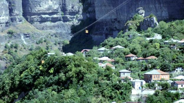 Ein bewaldeter Abhang mit einem kleinen Dörfchen, über das eine Seilbahn führt. Es sind zwei Gondeln sichtbar.