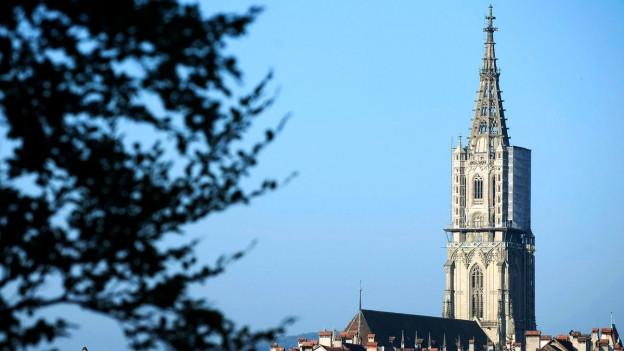 Eine Kirchengebäude, das in den Himmel ragt, davor die Berner Altstadt.