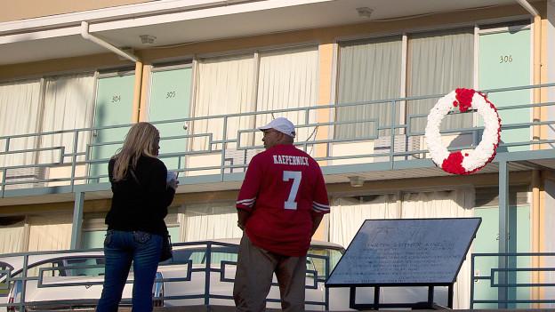 Zwei Personen stehen vor einem Motel.
