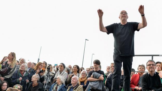 Ein Mann im T-Shirt beim Dirigieren unter freiem Himmel, hinter ihm stehen Leute.