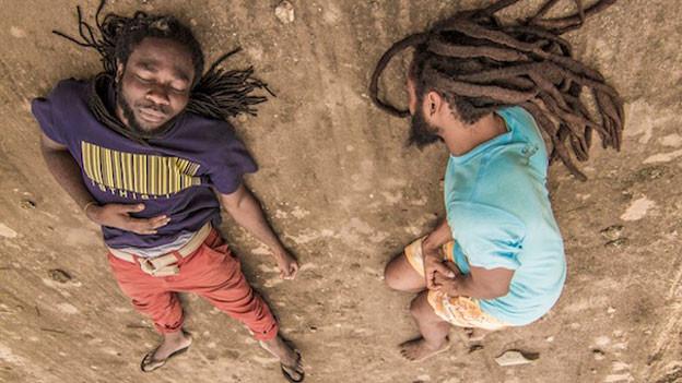 Man sieht zwei Männer mit Rastas, die auf dem Sand liegen.