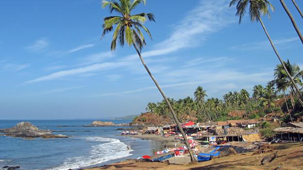 Die Insel Goa: ein Strand, hellblaues Wasser, blauer Himmel und ein paar Hütten.