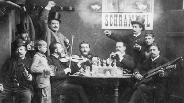 Schwarzweiss-Foto mit musizierenden Männern an einem Kneipentisch