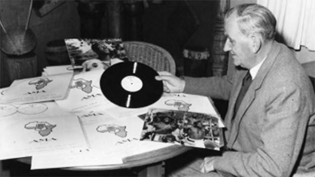 Hugh Tracey sitzt an einem Tisch und hält eine Schallplatte